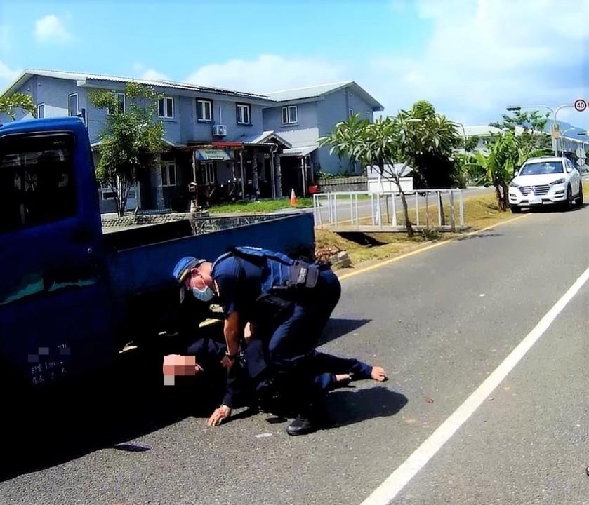 烈日當空老翁醉臥柏油路上 旗警貼心護送返家。(記者劉明吉翻攝)