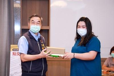 黃副市長贈送禮品給住戶鄭小姐。(記者林志強翻攝)