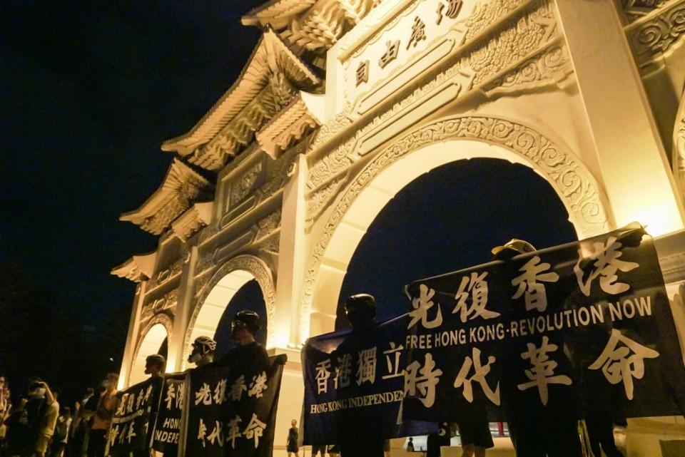 陳樂晞《不具名:自由的代價》劇照_一群在台香港人在自由廣場前舉「香港獨立」布條,